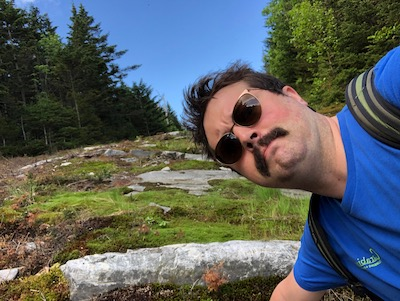 Zach's photo with a mustache on a mountain